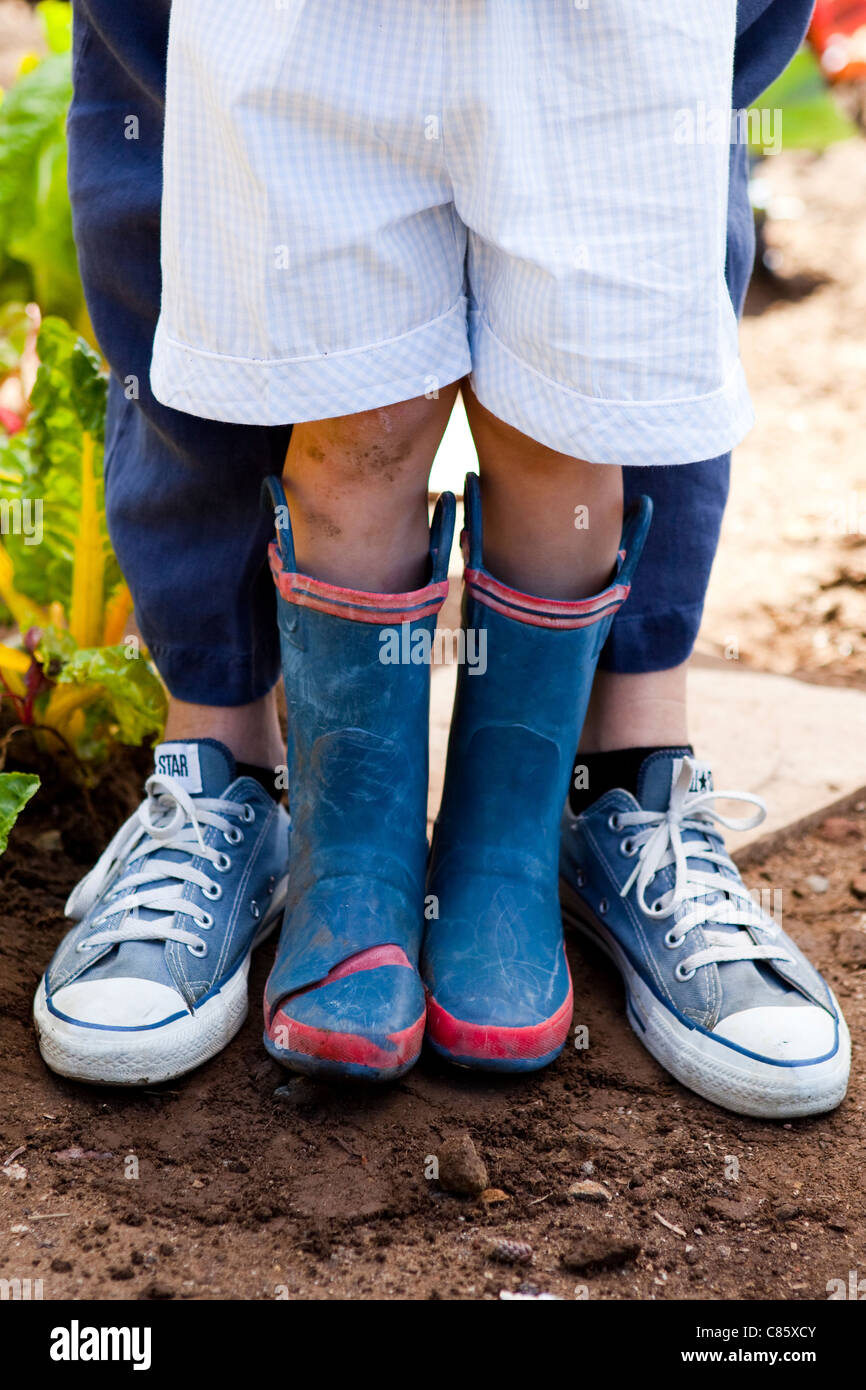 Little boy in rain boots and mom in sneakers - Stock Image