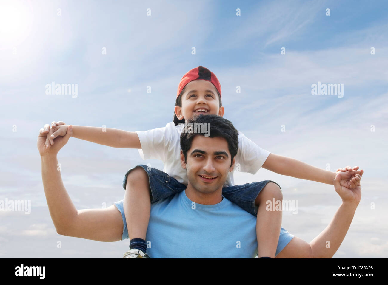 Son getting a piggyback ride from his father Stock Photo