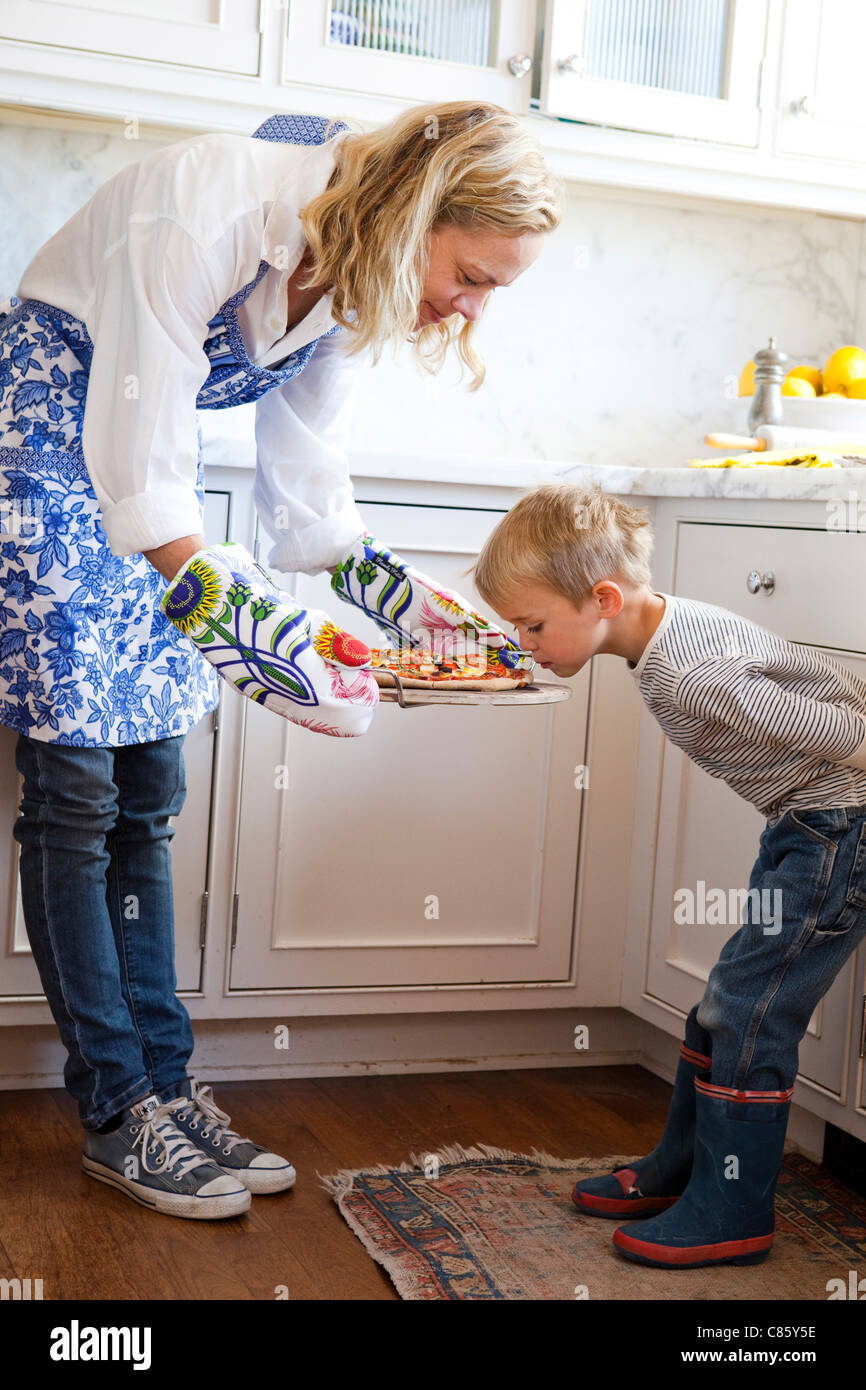 Little boy smelling fresh made pizza - Stock Image