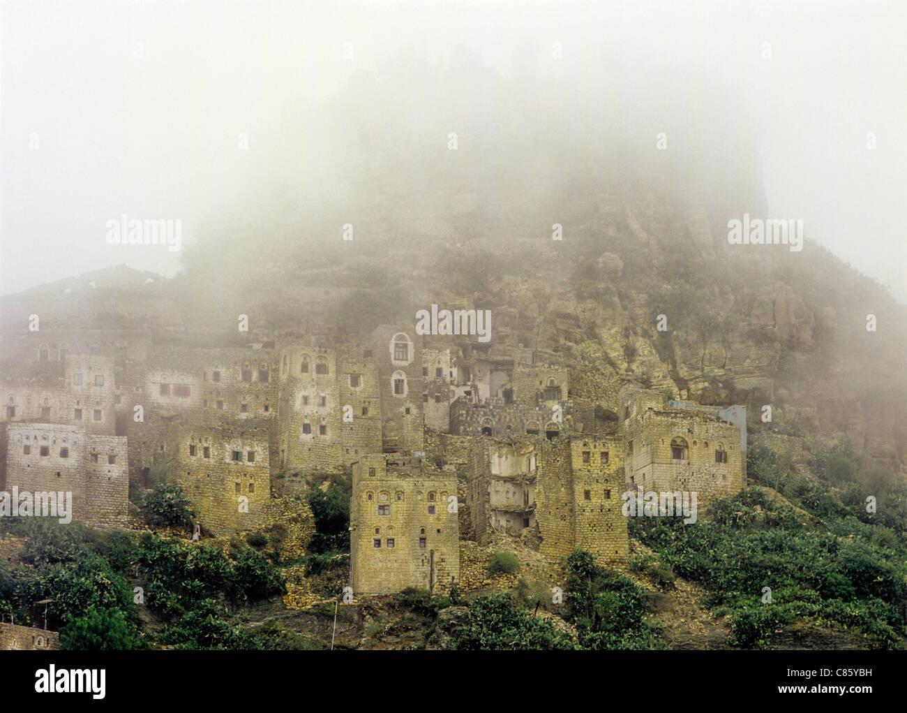 Fogged in town of mud brick multi-story buildings in Hajjah Governorate, Yemen - Stock Image
