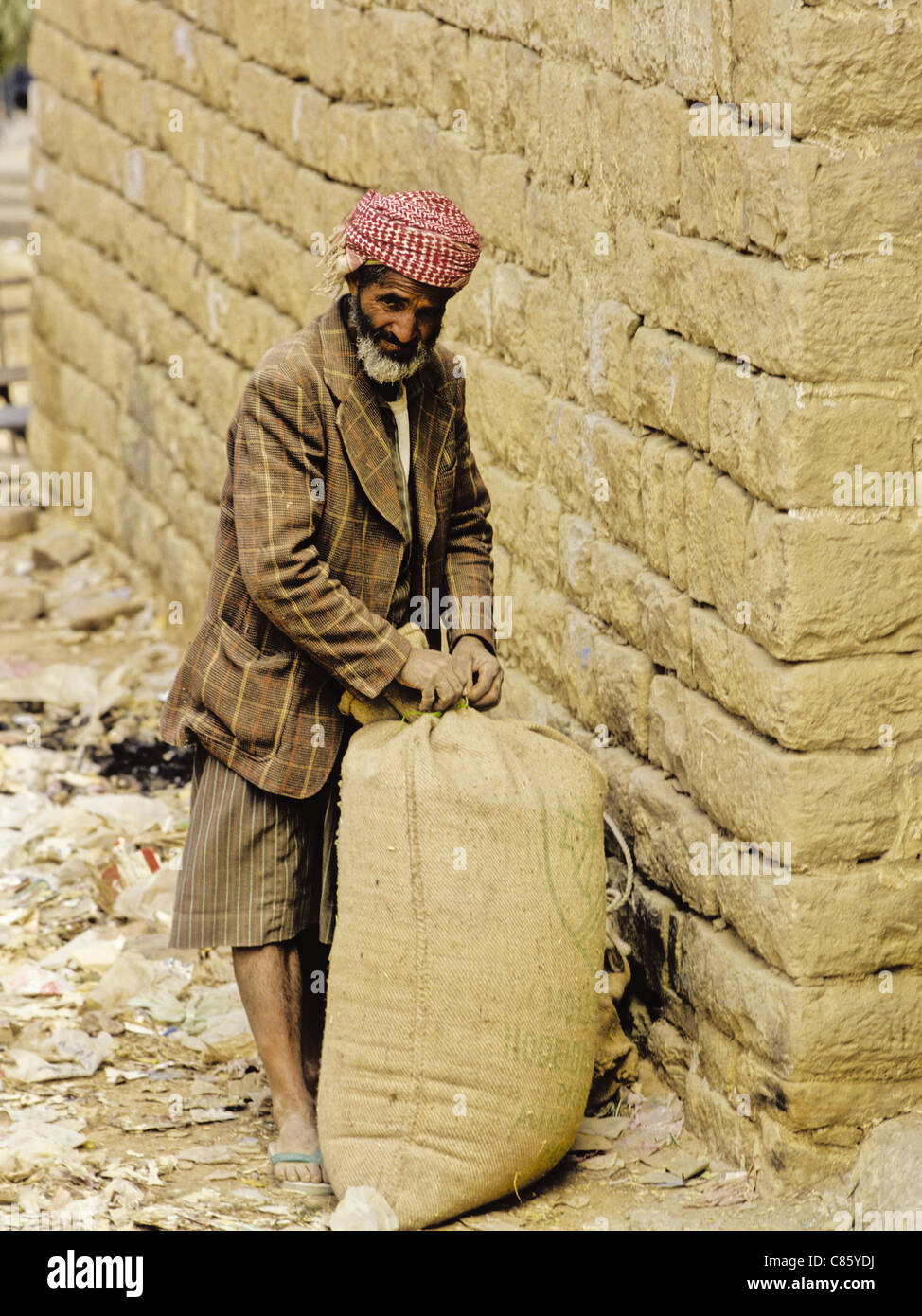 Full-length portrait of a Yemini man wearing a red and white checked keffiyeh and holding a burlap bag, Thula, Yemen - Stock Image