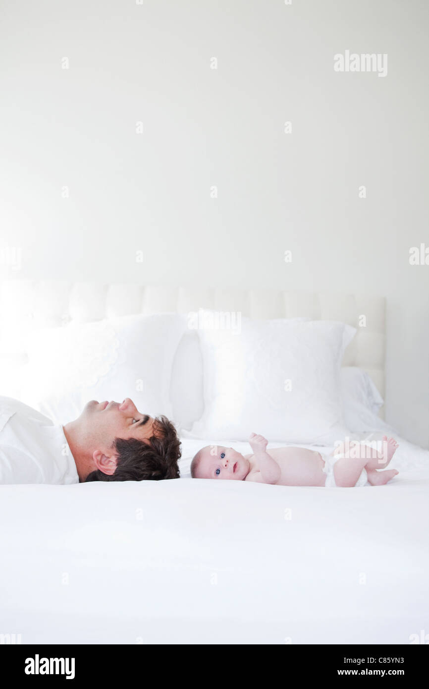 Dad and baby laying on bed - Stock Image