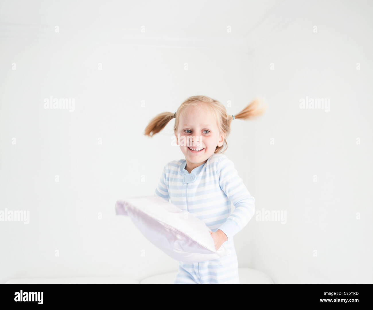 Little girl in striped pajamas - Stock Image