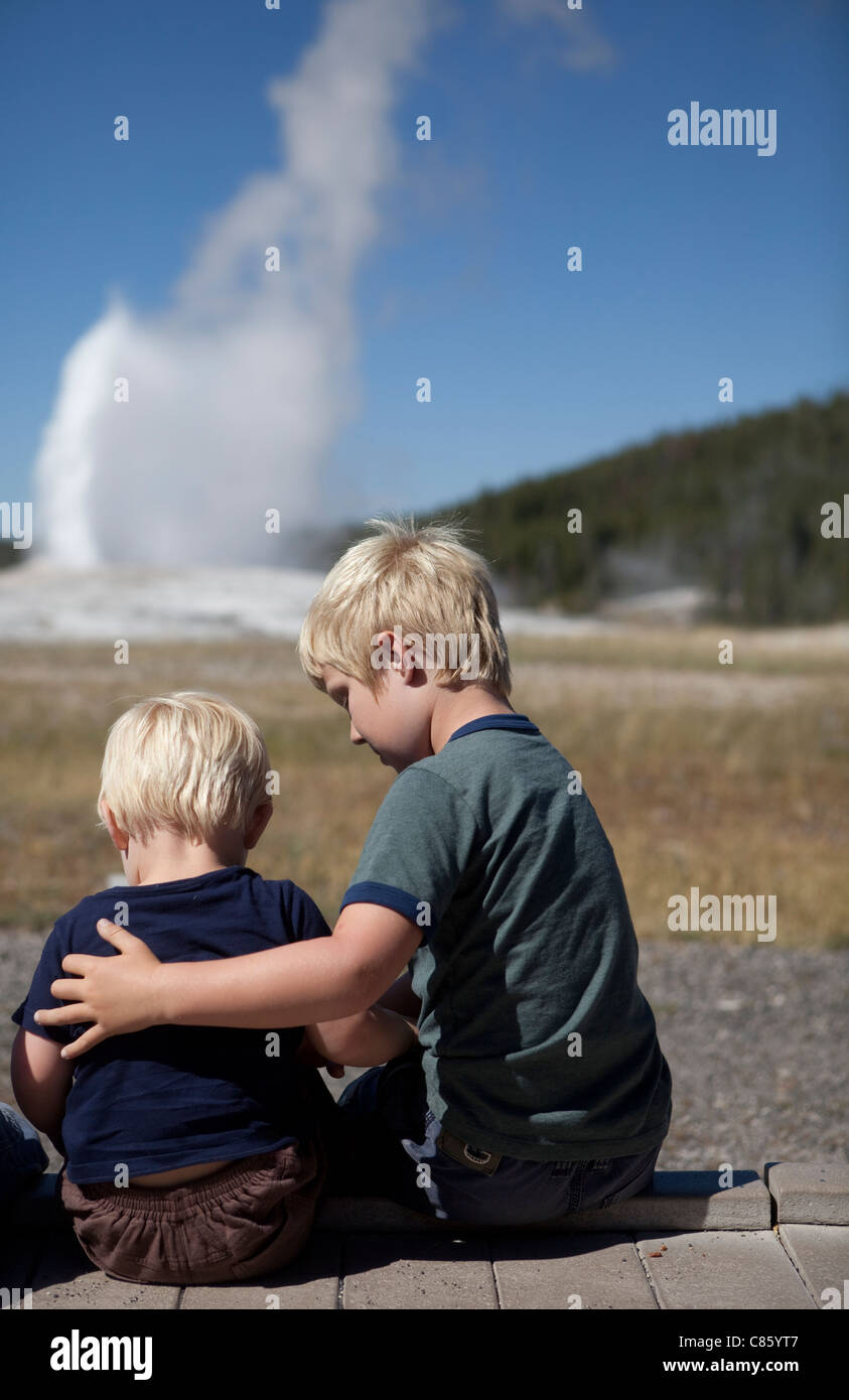 Brothers watching old faithful erupt - Stock Image