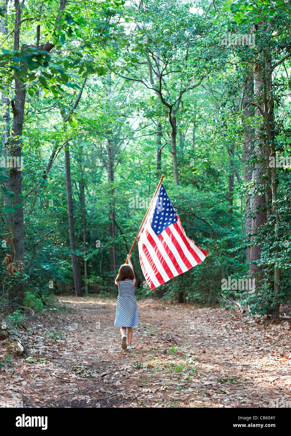 Little girl carrying an american flag through the woods - Stock Image