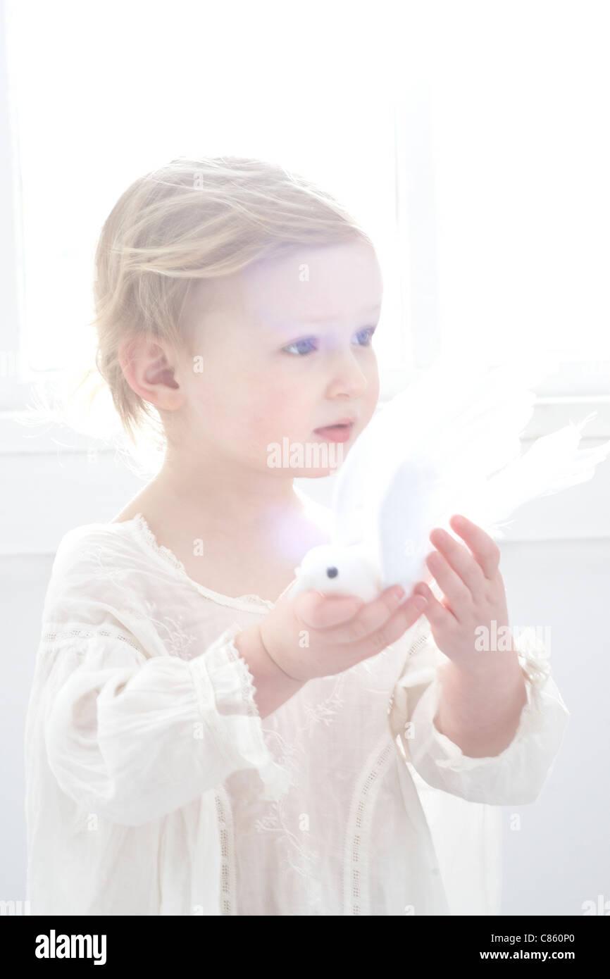 Little girl holding fake dove - Stock Image