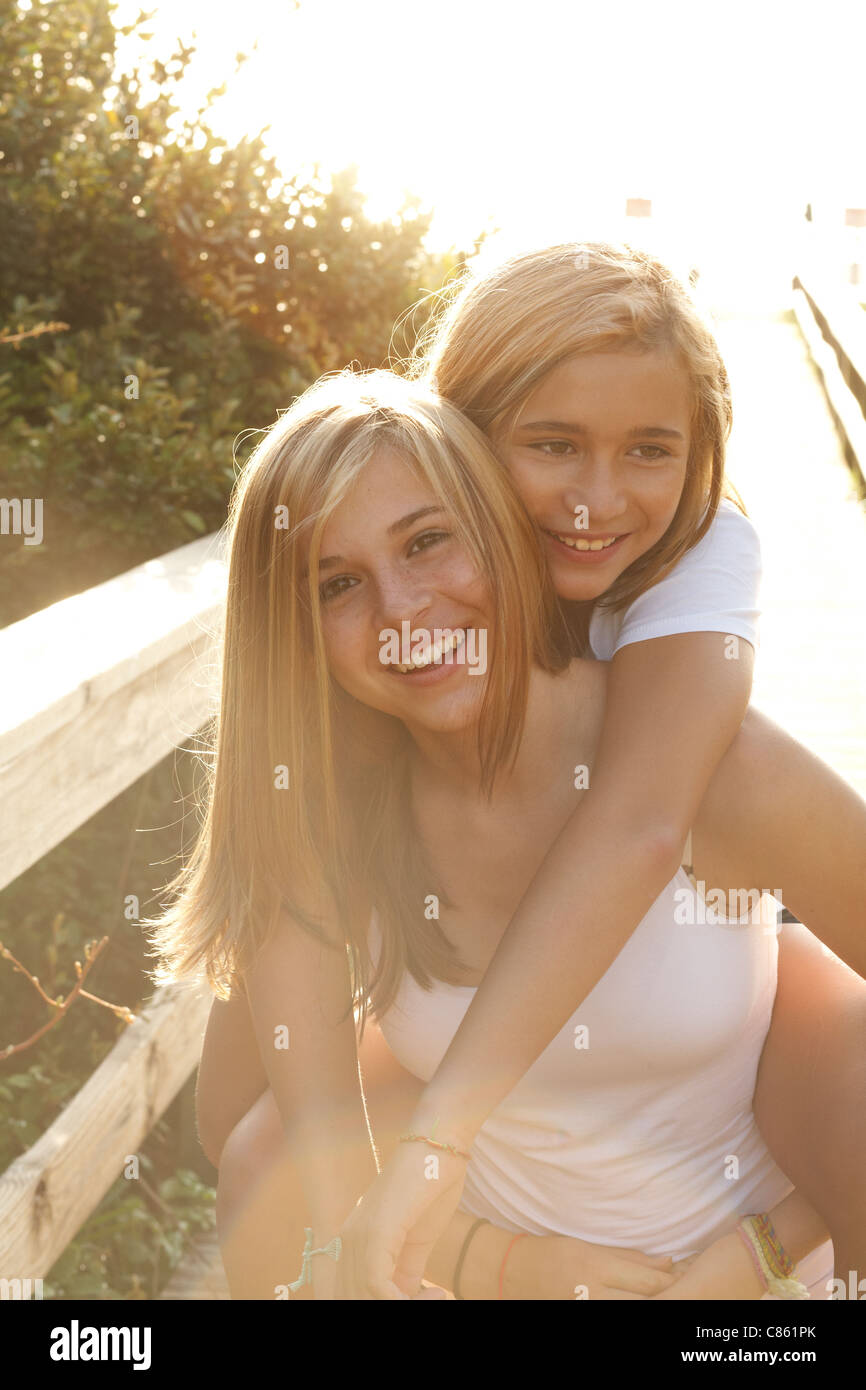 Sisters playing piggy back on the beach boardwalk - Stock Image