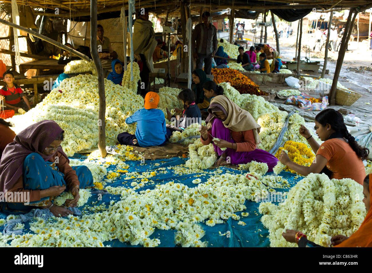 Indian women and children at work stringing garlands at Mehrauli Flower Market, New Delhi, India - Stock Image