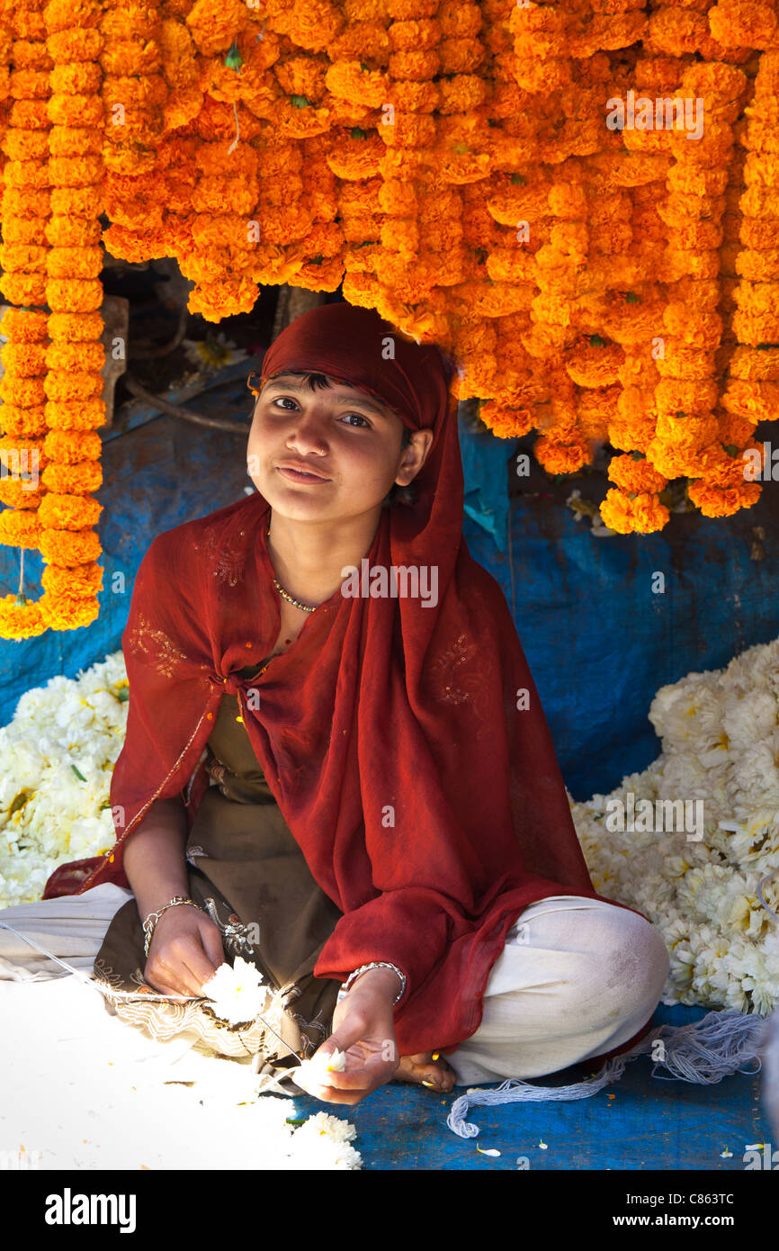 Young Indian girl stringing marigolds in ceremonial Brahmin garlands at Mehrauli Flower Market, New Delhi, India - Stock Image