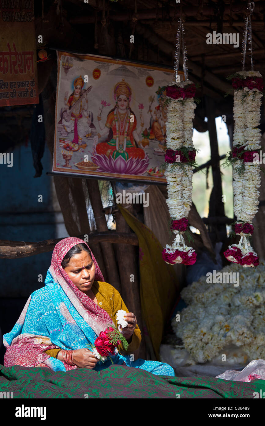 Indian woman at work stringing garlands at Mehrauli Flower Market, New Delhi, India - Stock Image