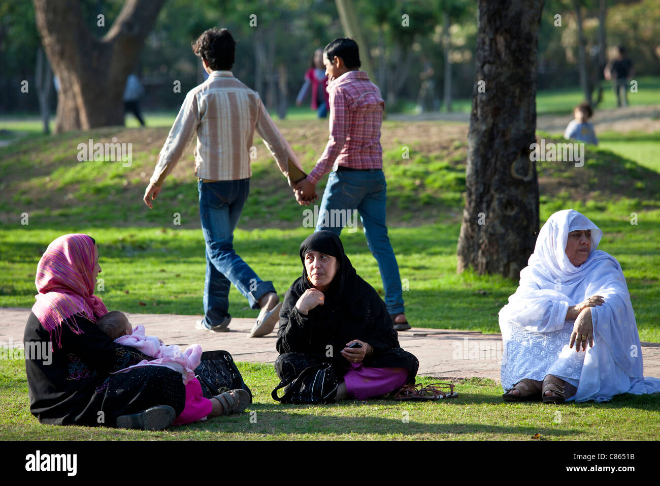 Men holding hands and muslim women with child in gardens at Humayuns Tomb, in New Delhi, India - Stock Image