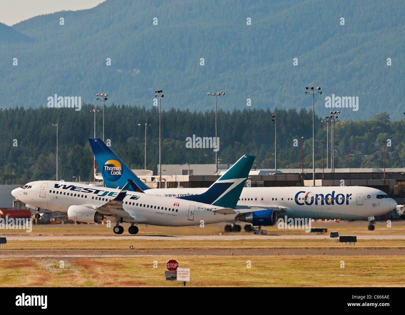 Airliners: a Westjet Boeing 737 takes off as a Condor (Thomas Cook) Boeing 767 taxis to position at Vancouver's - Stock Image