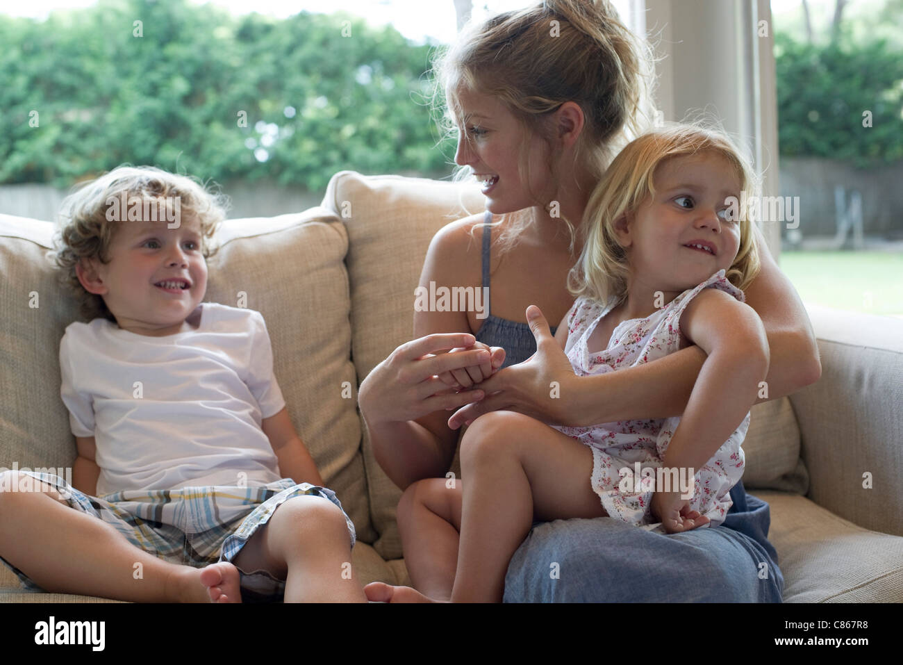 Mother and two young children sitting together on sofa - Stock Image