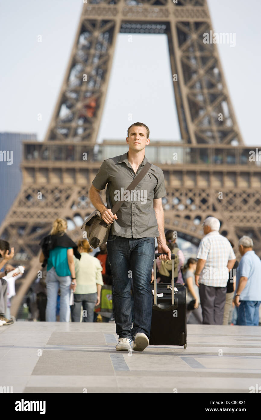 Male tourist walking with luggage, Eiffel Tower, Paris, France - Stock Image