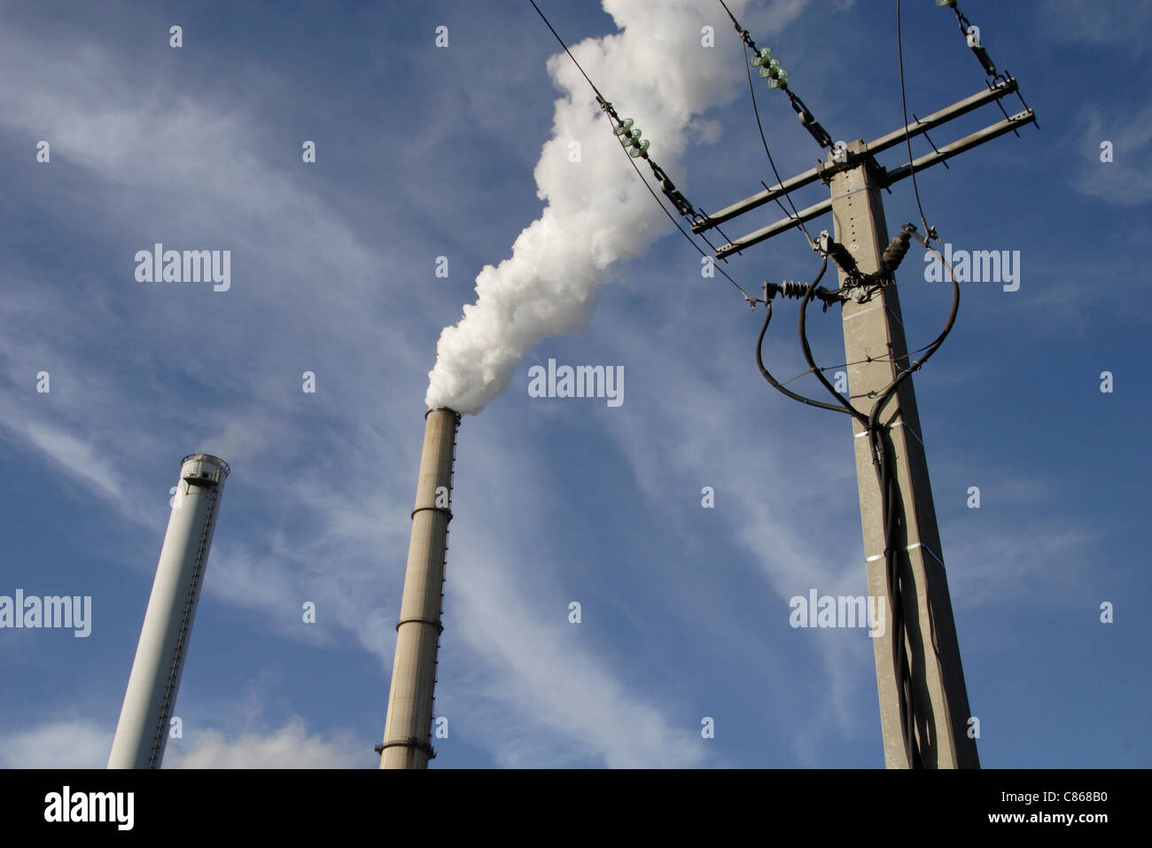 Electric post and smokestack against sky - Stock Image