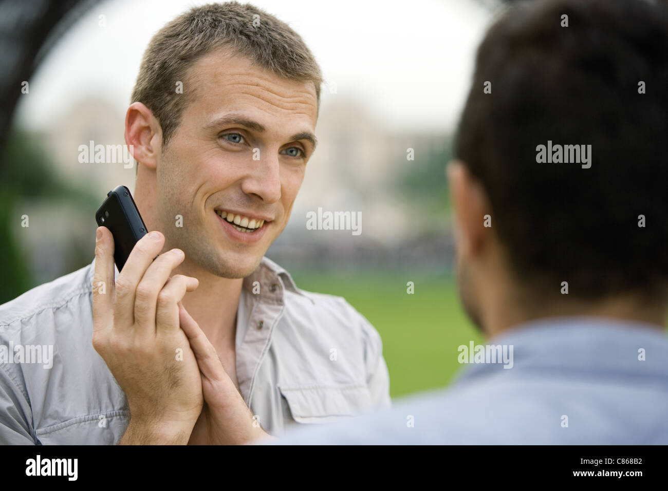 Man on phone call, covering cellphone mouthpiece with hand to talk to acquaintance - Stock Image