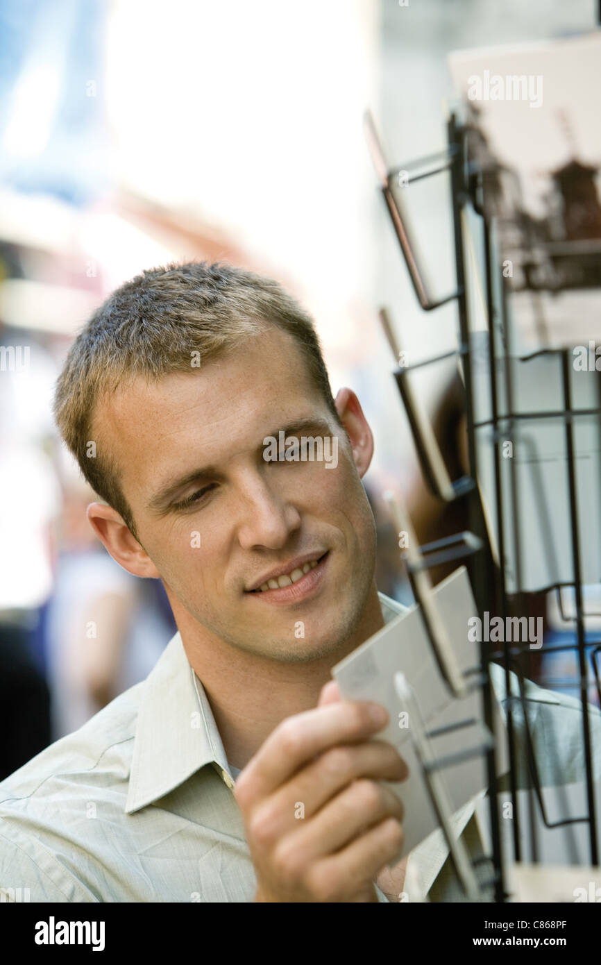 Male tourist looking at postcards - Stock Image
