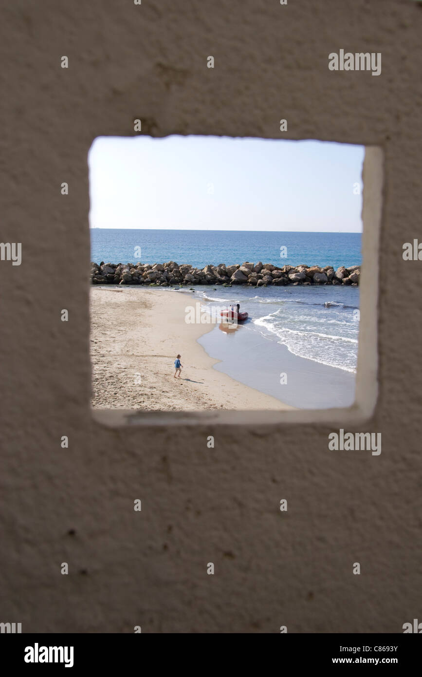 View of beach and ocean through window - Stock Image