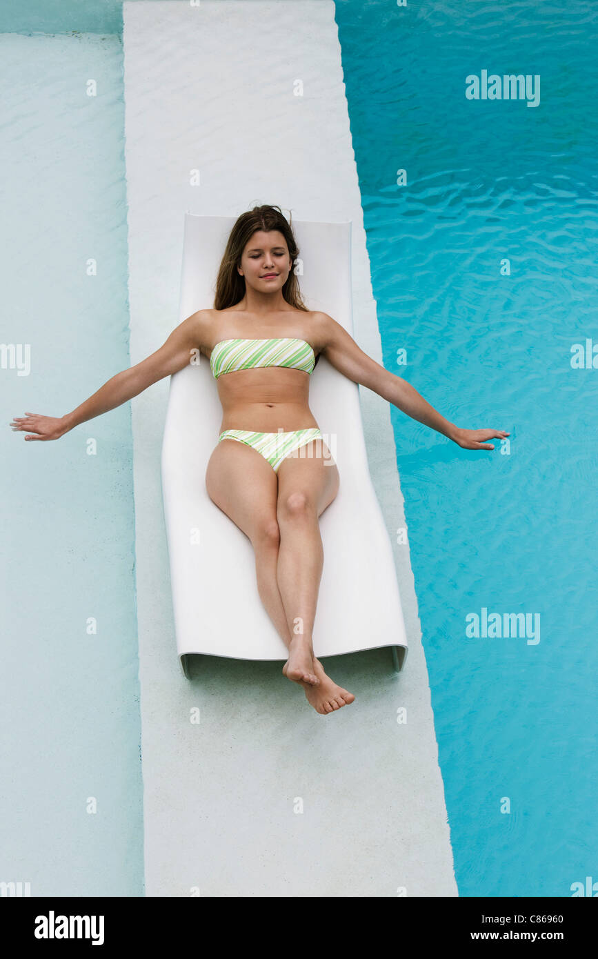 Young woman reclining on deck chair on walkway between swimming pools - Stock Image