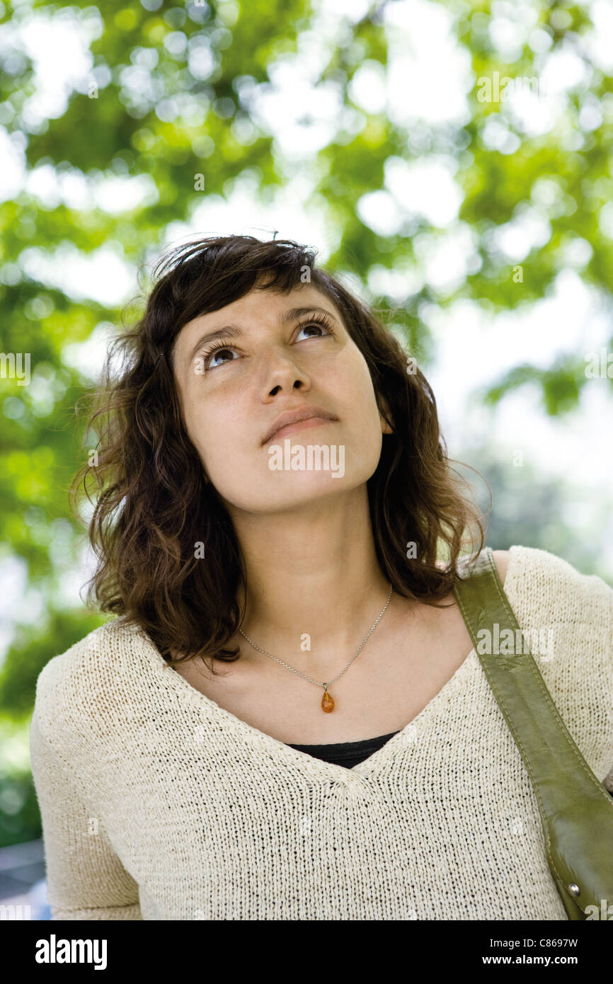 Woman looking up, portrait - Stock Image