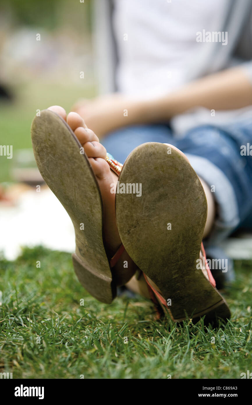 Woman sitting in grass with legs crossed at ankle, cropped - Stock Image
