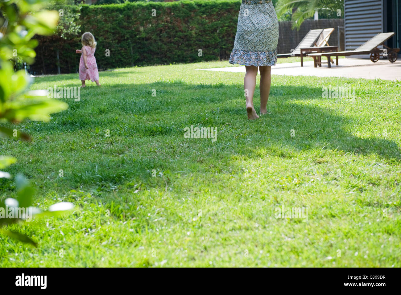 Mother and daughter walking in backyard Stock Photo