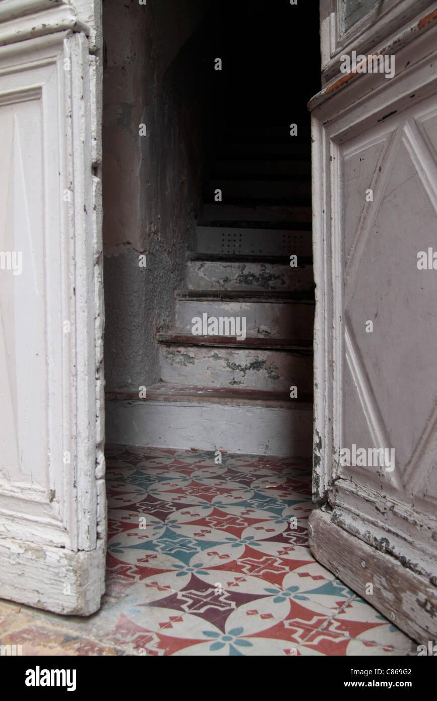 Half-open door leading to stairway - Stock Image