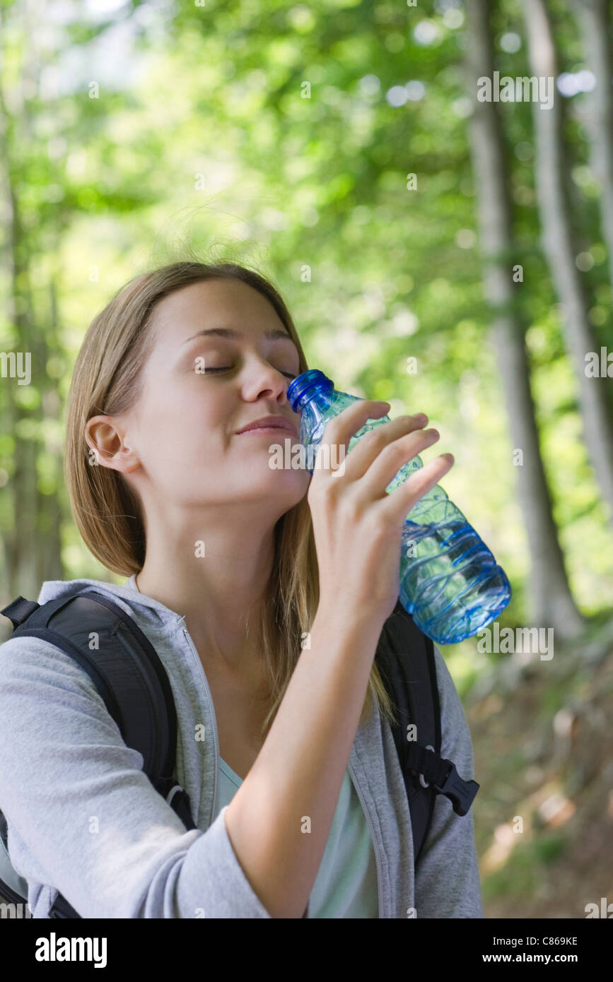 Woman drinking bottled water in woods - Stock Image
