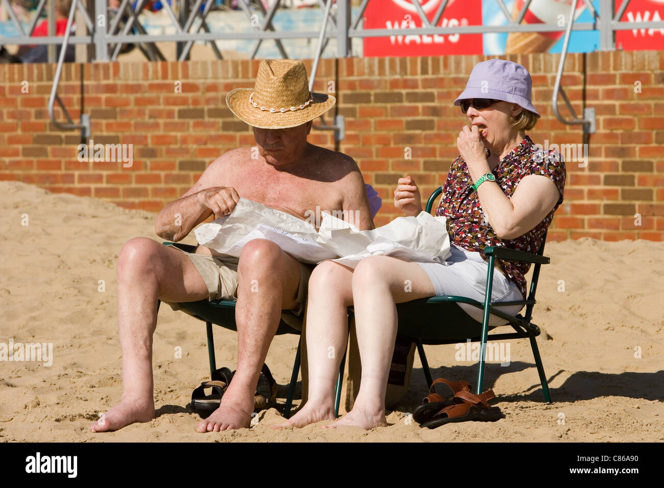 British tourists enjoying the sun on Camber Sands in East Sussex United Kingdom - Stock Image