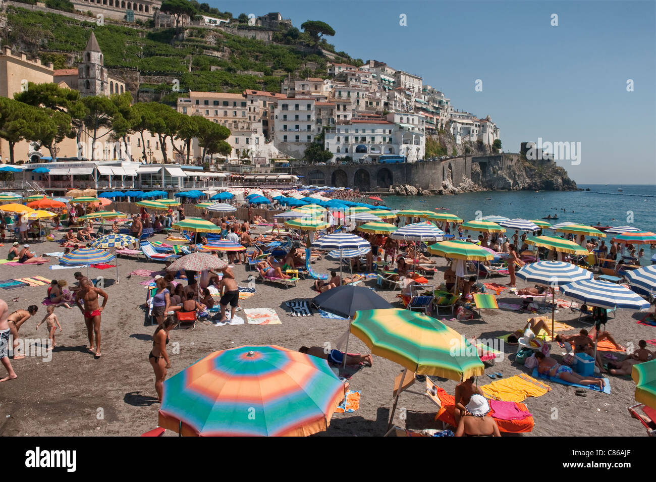 Amalfi, Italy. The tiny beach is packed with visitors in high summer - Stock Image