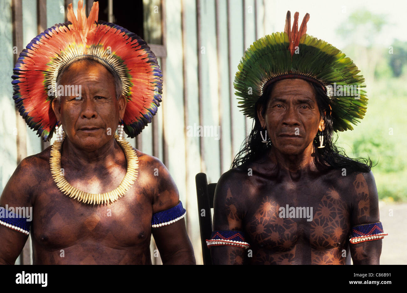 Altamira, Brazil. Two Kayapo Indian elders with bead amulets and tooth necklace wearing feather cocaa headdresses. - Stock Image