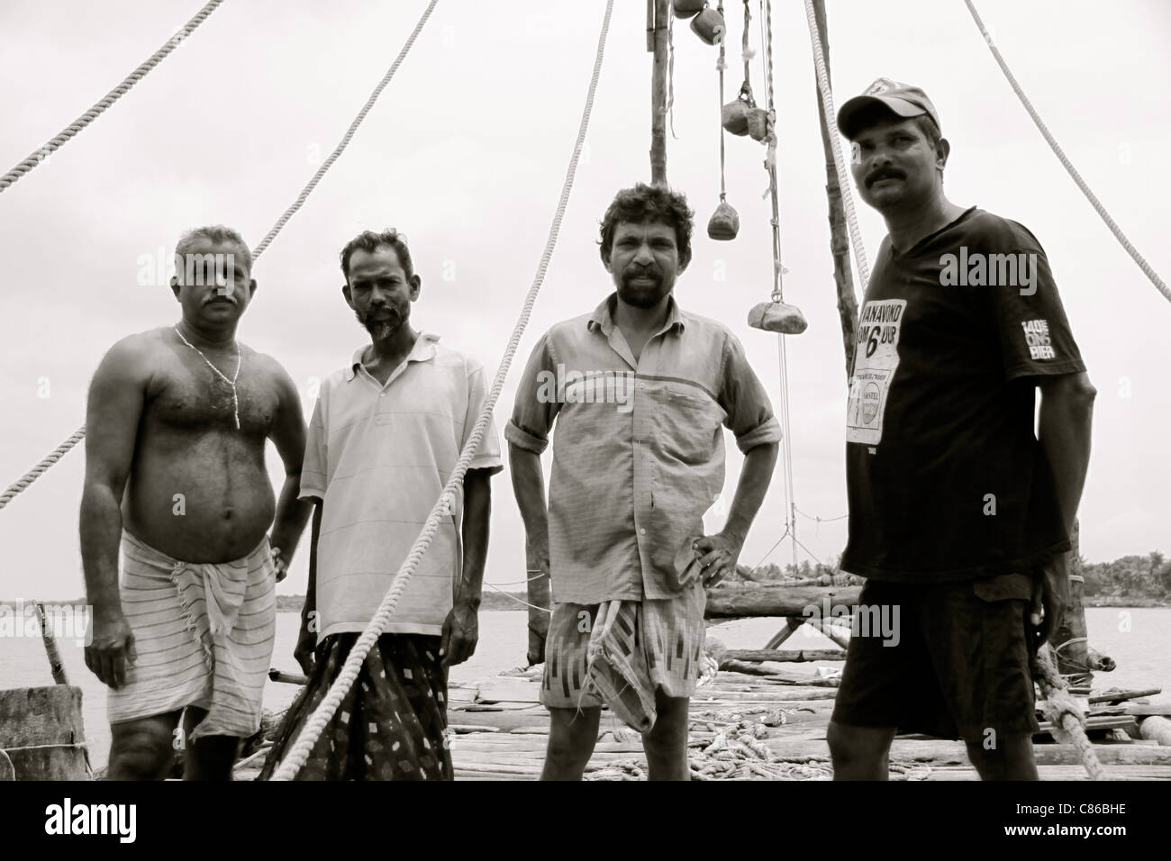 Four fishermen with their Chinese fishing nets in Kochi, Kerala, India - Stock Image