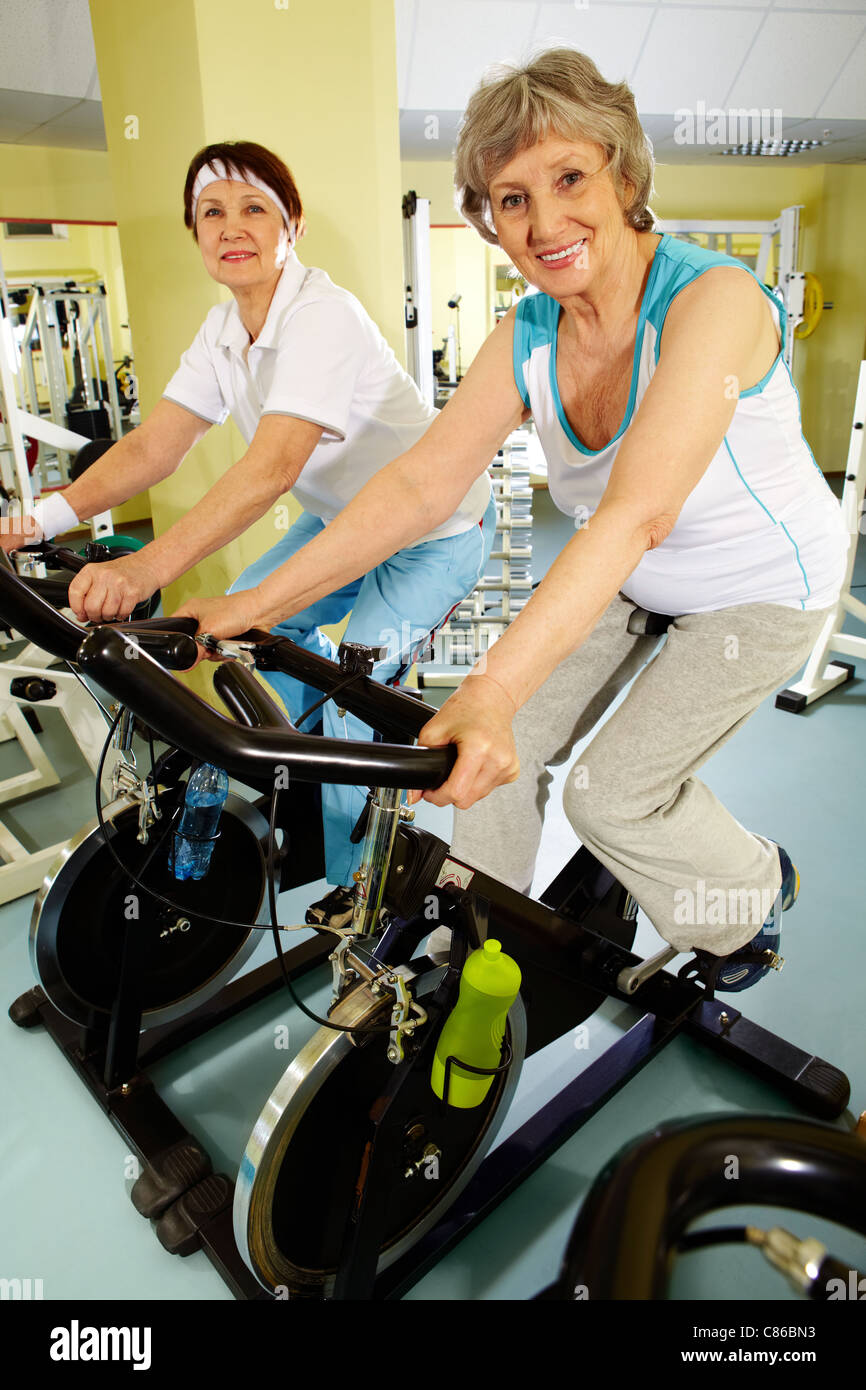 Two senior women training actively on exercise bicycles - Stock Image