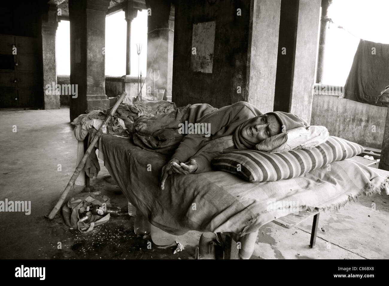 A dying woman lies on a bed in a derelict building, Varanasi, India - Stock Image