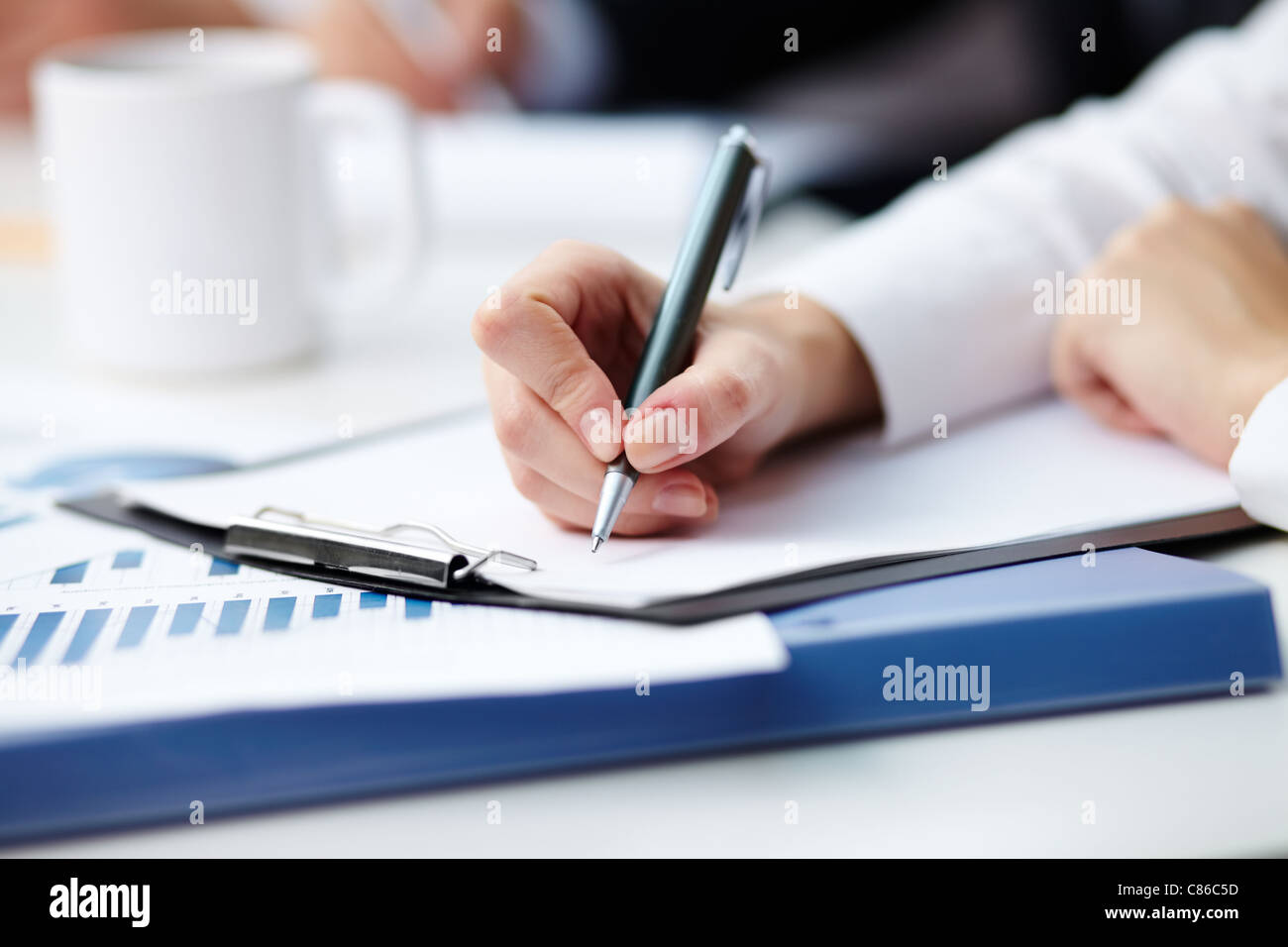 Close-up of female hand making notes - Stock Image