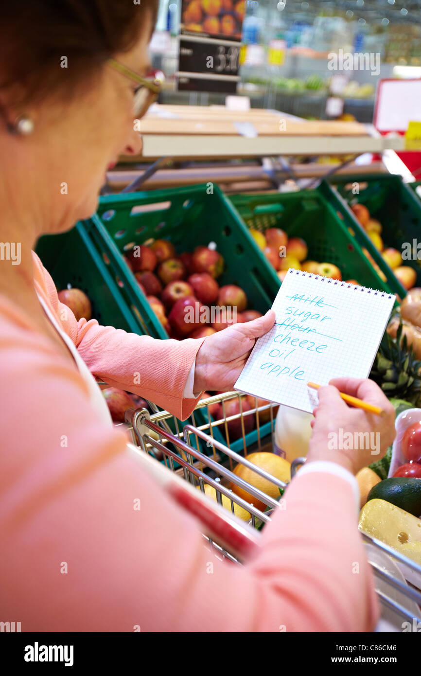 Image of senior woman looking at product list with goods in cart near by - Stock Image