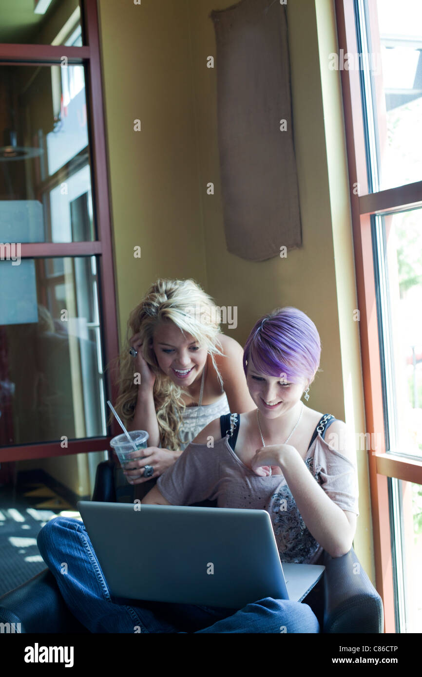 teens girls in coffee bar using laptop to surf the web - Stock Image