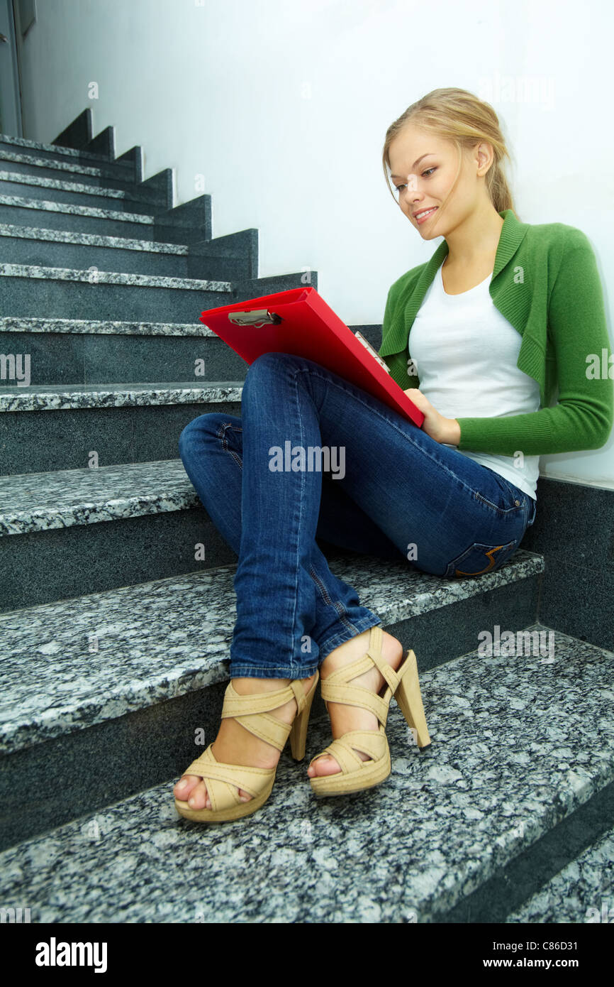 Photo of pretty girl with folder sitting on stairs of college by the wall - Stock Image