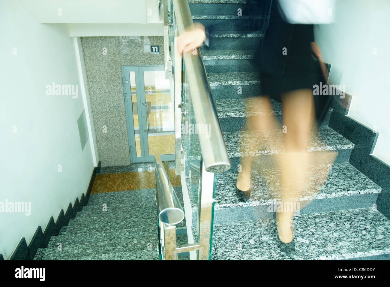 Blurred outline of businesswoman with briefcase going down the stairway - Stock Image