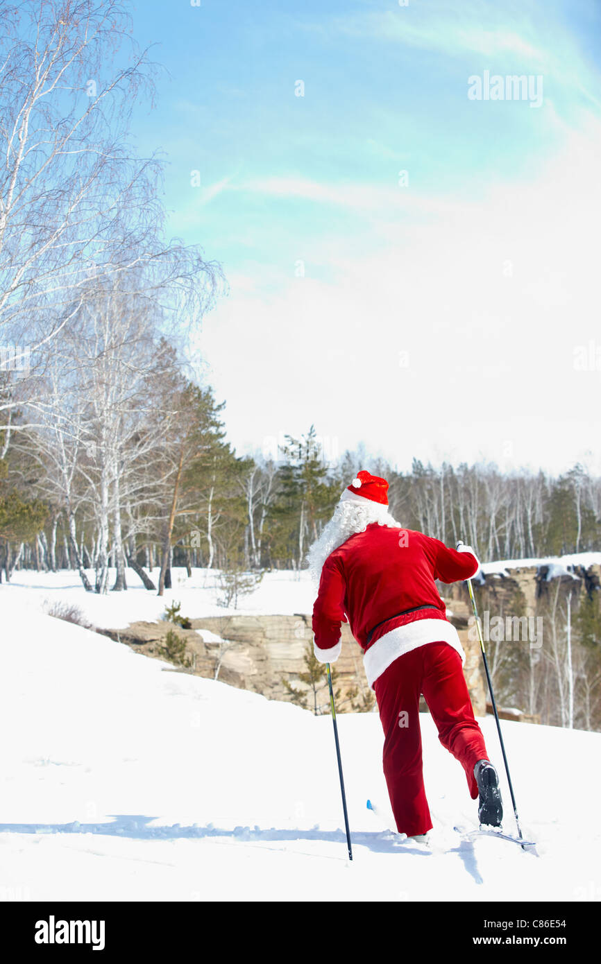 Santa Claus skiing in winter wood Stock Photo