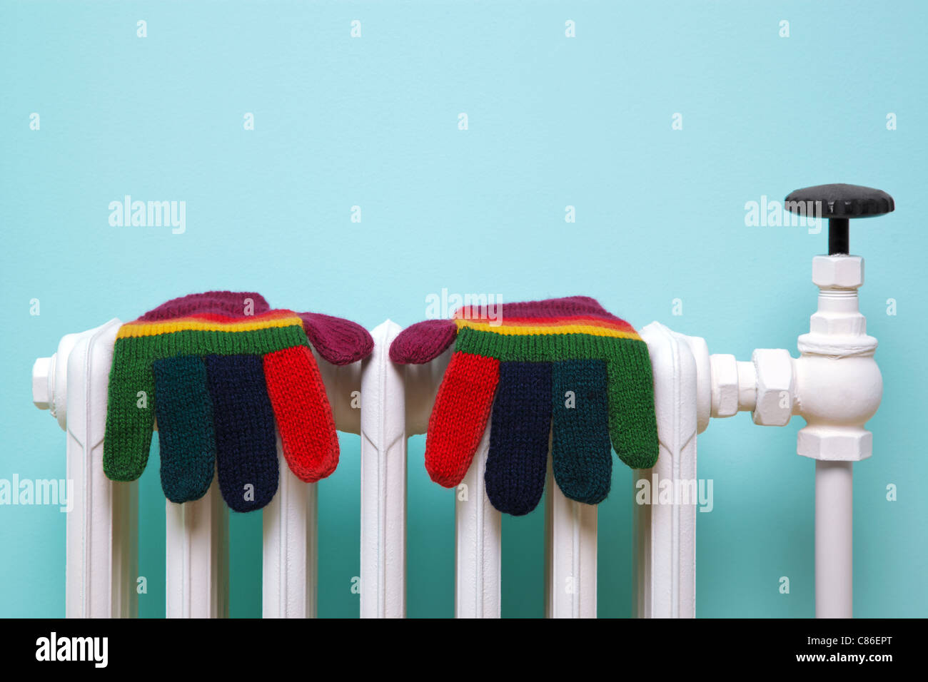 Photo of a pair of hand knitted striped woolen gloves drying on an old traditional cast iron radiator. - Stock Image