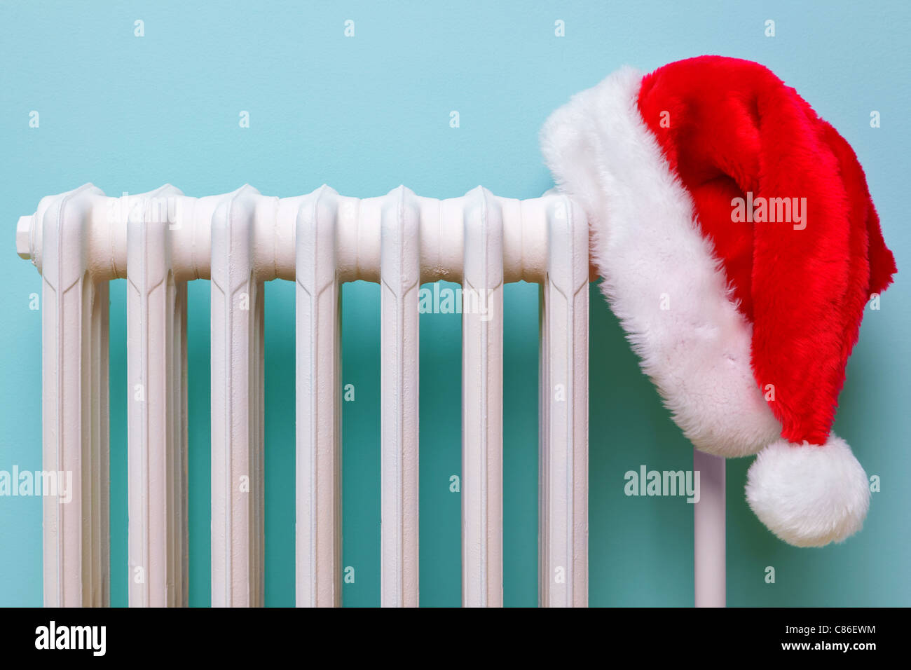 Photo of a red and white Father Christmas hat hanging on an old traditional cast iron radiator. - Stock Image