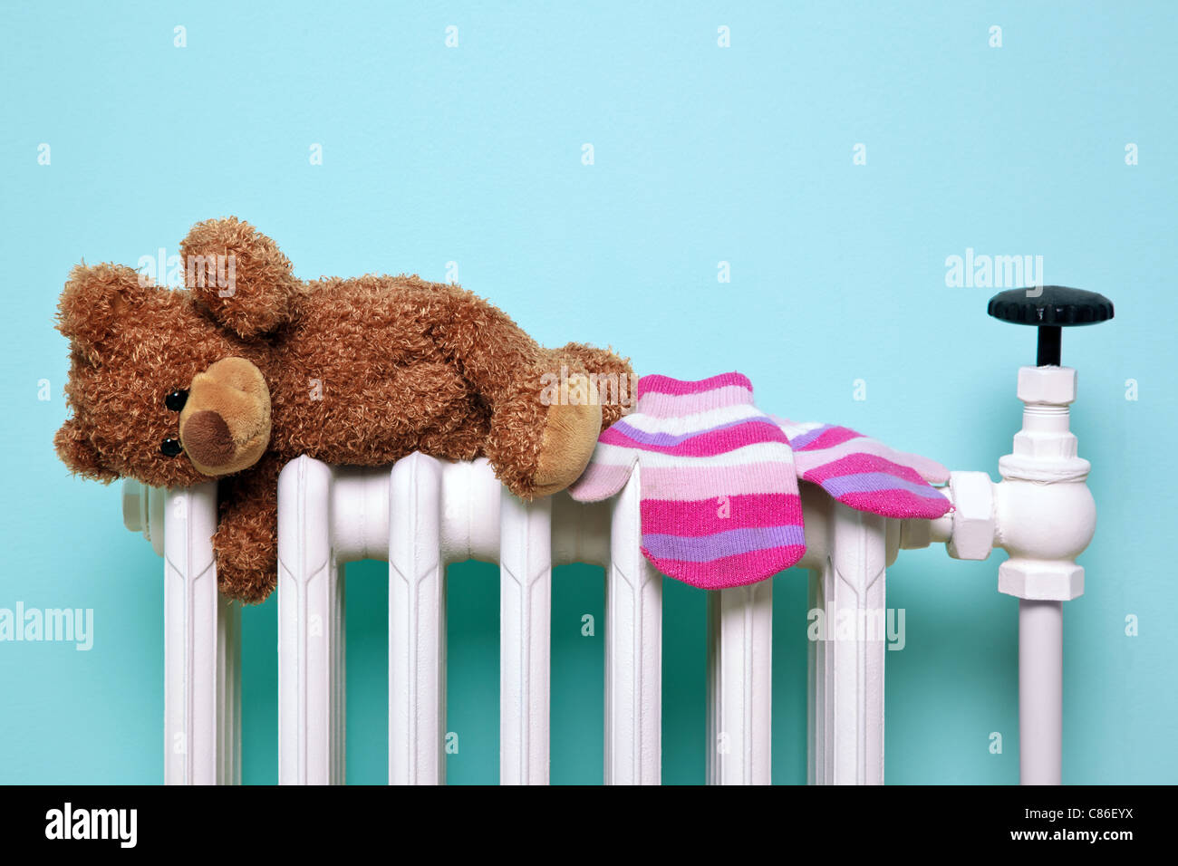 Childs teddy bear and gloves drying on a radiator - Stock Image