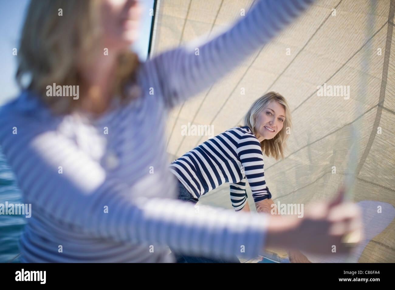 Women adjusting sails on boat - Stock Image