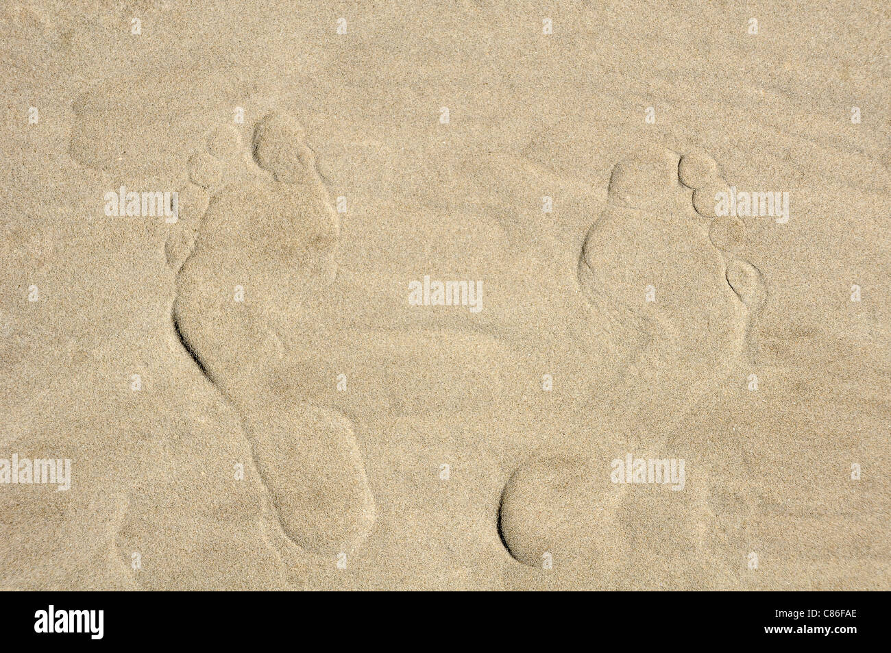 golden sand background with two foot prints - Stock Image