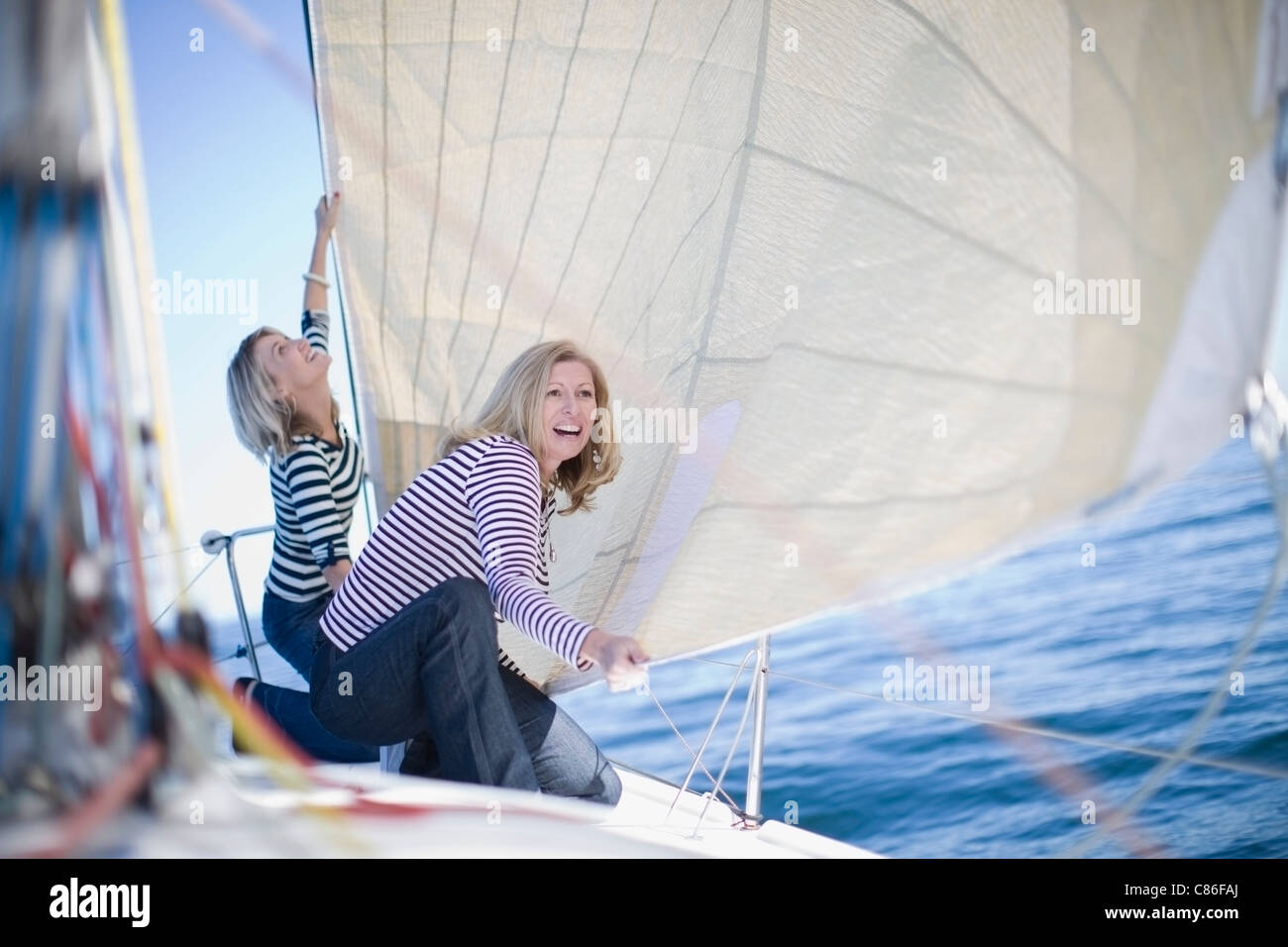 Women adjusting sail on boat - Stock Image