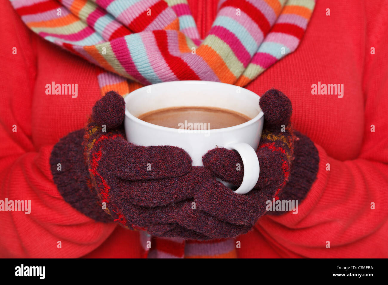 Close up midriff photo of a woman wearing a red jumper, woolen gloves and a scarf holding a mug full of hot chocolate - Stock Image