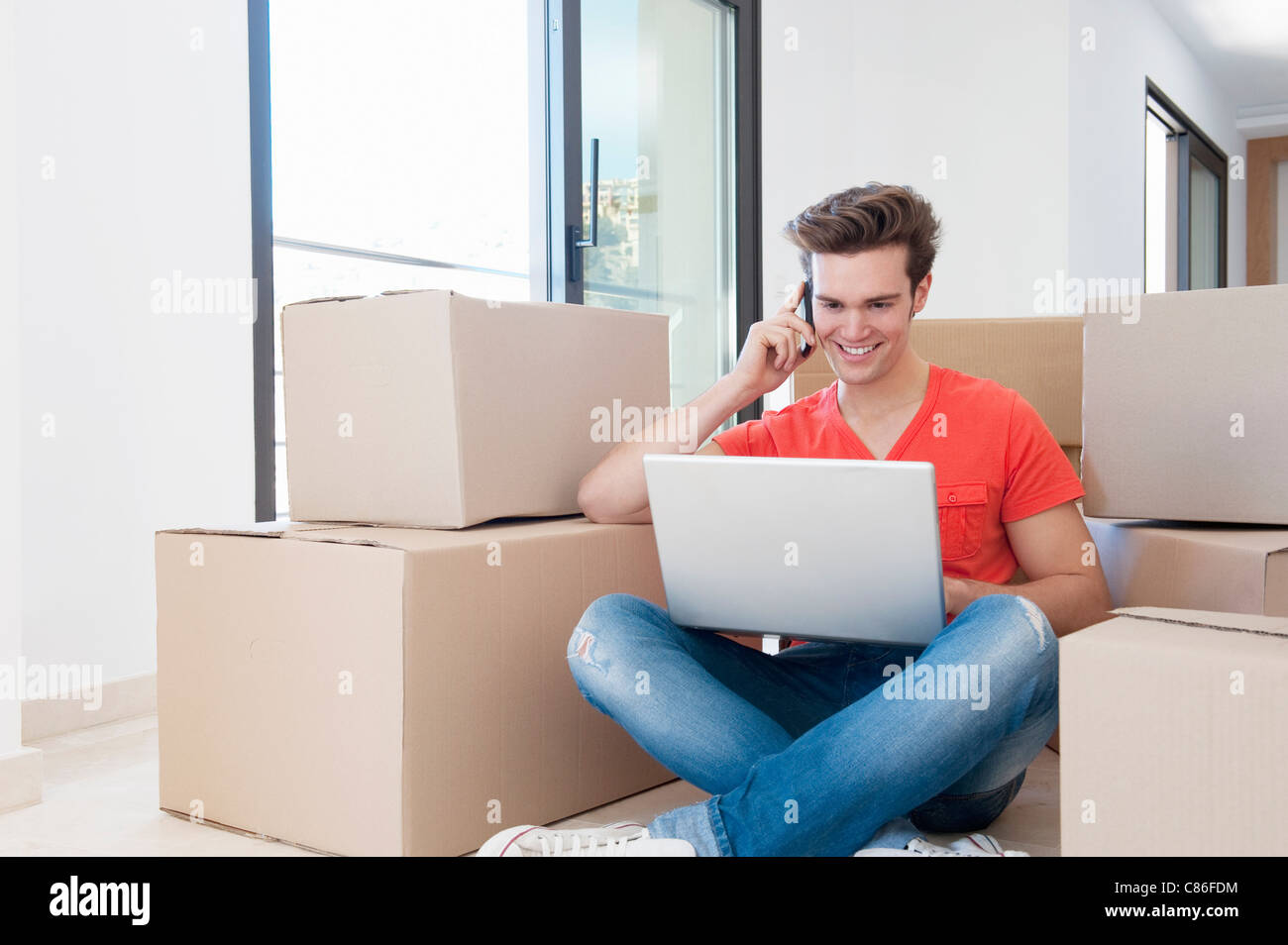 Man using laptop in new home - Stock Image