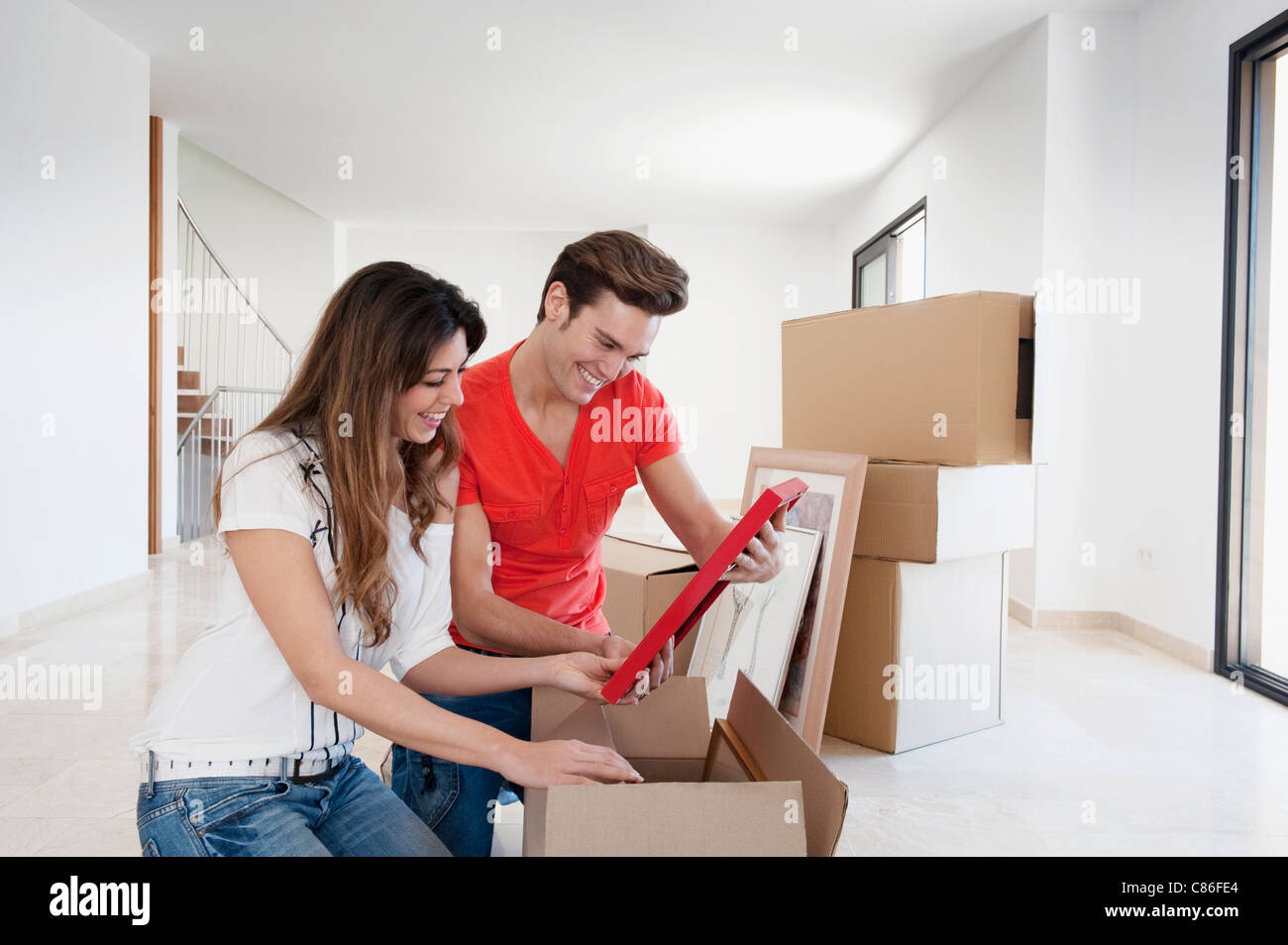 Couple unpacking box in new home - Stock Image
