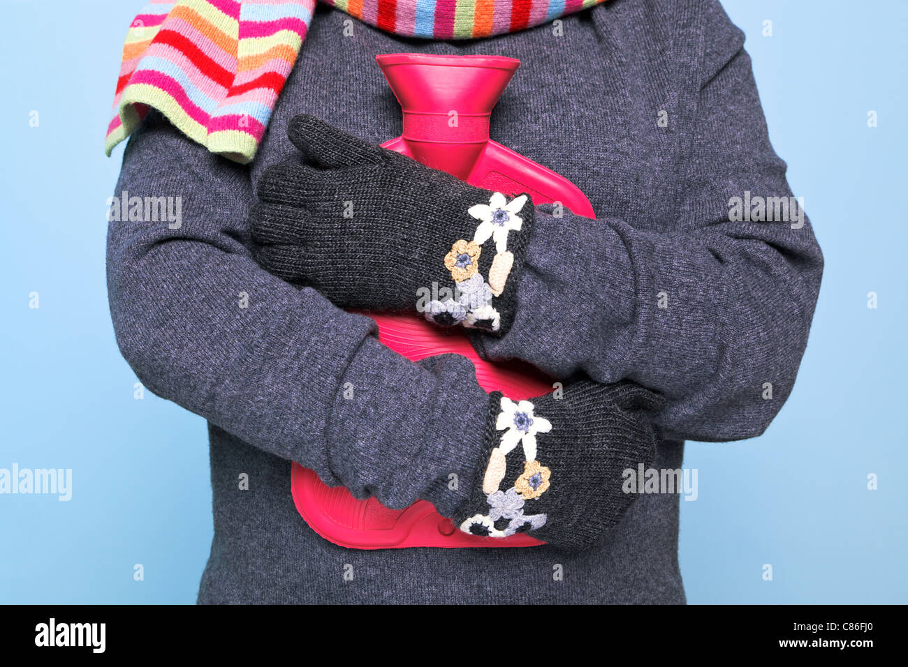 Photo of a woman holding a red hot water bottle to her chest whilst wearing hand kniited woolen gloves trying to - Stock Image